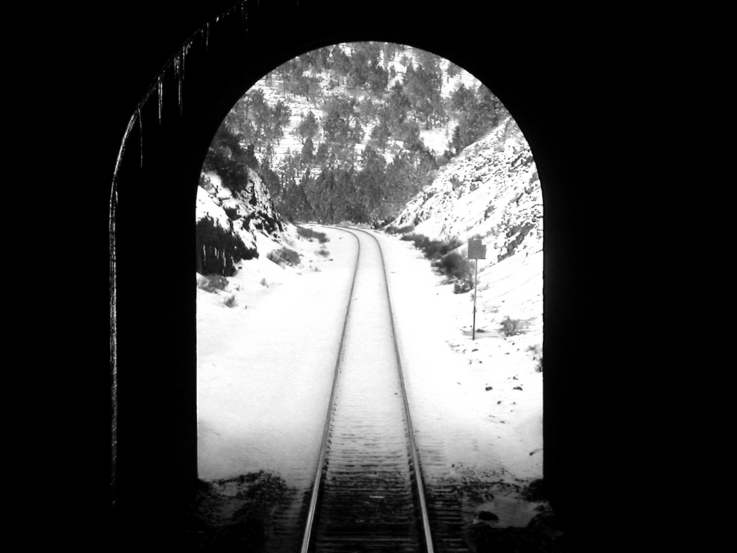 Railroad tracks in the snow from inside a tunnel